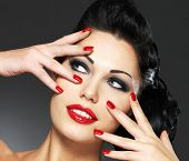 Beautiful fashion woman with red nails, creative hairstyle and makeup - Model posing in studio