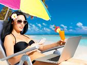 Young woman on the beach with a laptop and mobile phone sending message. Vacation and communication
