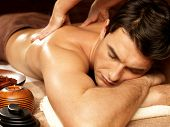 foto of shoulders  - Masseur doing back massage on man body in the spa salon - JPG