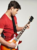 Guitarist plays on the electric guitar with bright emotions on grey  background