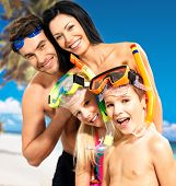 Portrait of  happy fun beautiful family with two children at tropical beach with protective swimming