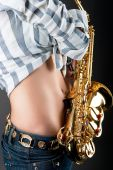sexy stomach of young pretty blonde girl with saxophone