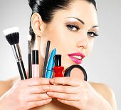 Beautiful woman with makeup brushes near her face. Pretty girl poses at studio with cosmetic tools