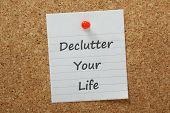 image of discard  - The phrase declutter your life typed on a piece of lined paper and pinned to a cork notice board - JPG