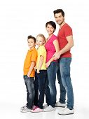 Full portrait of happy young family with two children standing together in line - isolated on white