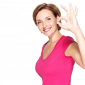 Portrait of a beautiful adult happy woman with ok gesture over white background