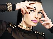 Beautiful face of fashion woman with black nails and bright makeup.  Sexy stylish girl with bracelet