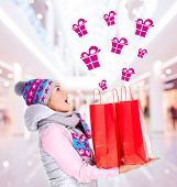 Photo of the surprised woman with gifts after shopping to the new year at shop