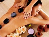 foto of stone-therapy  - Adult woman having hot stone massage in spa salon - JPG