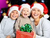 Happy mother with children holds the new year gift on the christmas holiday - indoors