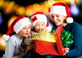 Mother with children opens the box with gifts on the christmas holiday - indoors
