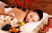 stock photo of backbone  - Adult woman relaxing in spa salon with hot stones on back - JPG