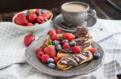 foto of eclairs  - Chocolate eclairs and fresh berries on plate with cup of coffee on the background - JPG