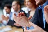 Photo of business partners�?�¢?? hands applauding at the meeting