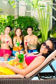 Asian friends partying and drinking fancy cocktails at hotel or club pool party