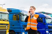 Logistics - female forwarder or supervisor with mobile phone, in front of trucks and trailers, on tr