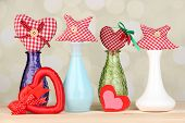 Hand-made textile hearts and stars on wooden table, on light background