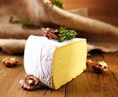 Tasty Camembert cheese with thyme and nuts, on wooden table