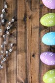Easter eggs and pussy-willow bud on wooden background