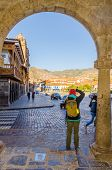 CUZCO, PERU, MAY 1, 2014: Female tourist takes photos of Plaza de Armas. This  square is considered the heart of Cusco