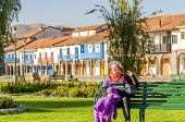 CUZCO, PERU, MAY 1, 2014: Mature female tourist rests on bench on Plaza de Armas. This  square is considered the heart of Cusco