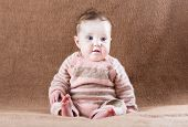 Sweet Baby Girl In A Warm Knitted Suit Sitting On A Brown Camel Wool Blanket