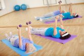 Mature women doing exercise with barbells in gym