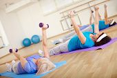 Mature females doing exercise with barbells in sport club