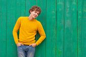 Smiling Curly Man In Yellow Sweater On Green Wooden Background