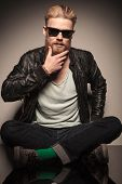 Fashion man in leather jacket looking down, sitting and holding his hands, studio shot