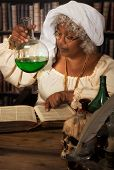 Old time alchemist working in her laboratory with green poison in a flask