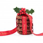 Chocolate chip cookie biscuit stack with holly and merry christmas red ribbon over white background.