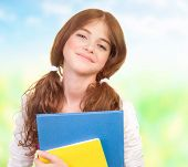 Closeup portrait of happy cute teen girl with textbooks having fun outdoors, back to school, educati