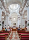 DUBROVNIK, CROATIA - MAY 26, 2014: People in church inside the Monastery of the Friars minor. Church is popular place for staging of musical concerts as well as a place of great sacramental importance