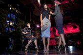 Three beautiful models in a stylish designer clothes posing in a nightclub