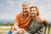 Portrait Of Happy Mature Couple Sitting On Bench Outdoor And Looking At Camera