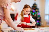 Family of mother and daughter baking gingerbread cookies at home on Christmas eve