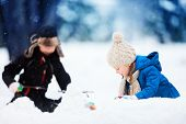 Little kids outdoors on a beautiful winter day playing with snow