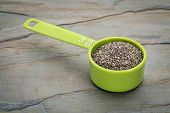 chia seeds in a green measuring cup against slate rock background