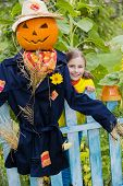 Autumn, Scarecrow and happy girl  in the garden