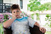 A Boy In A Wicker Chair On The Terrace