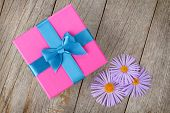Purple gift box and gerbera flowers on wooden table background