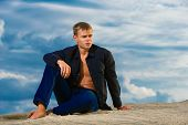 Young Handsome Man Is Sitting On The Sand On The Beach. Looks Thoughtfully Into The Distance. The Sk