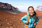 Woman walking and smiling happy, looking at beautiful nature landscape of mountain, East Maui Volca