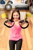 Asian woman doing strength exercise in fitness center.