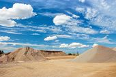 picture of sand gravel  - Sand and gravel quarry construction site with cloudy blue sky - JPG