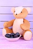 Toy bear and bowl of plums on wooden table on wooden wall background