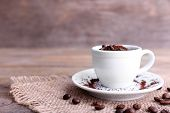 stock photo of sackcloth  - Mug of coffee beans and ground coffee on sackcloth on wooden table on wooden  background - JPG