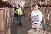 Pretty warehouse manager checking inventory in a large warehouse