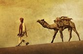 Indigenous Indian man walking through the desert with his camel.
